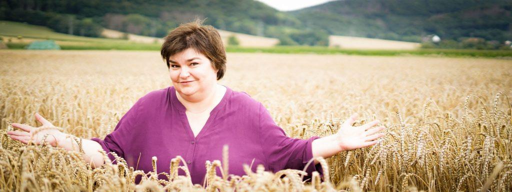 Bettina Luther zeigt auf ein Weizenfeld