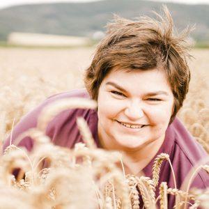 Bettina Luther lacht in einem Weizenfeld